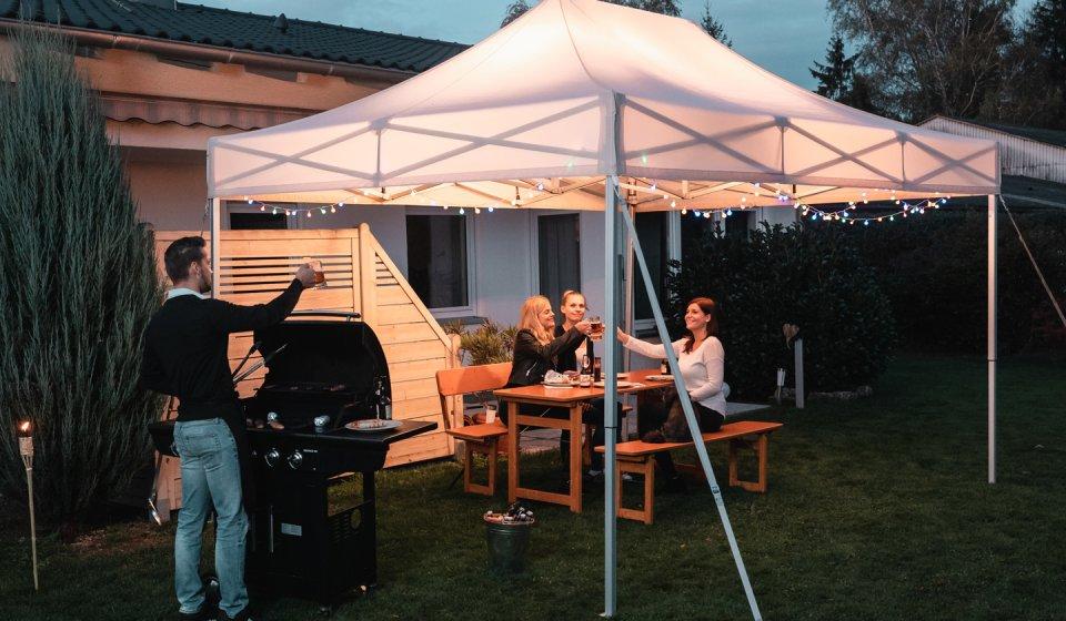 Der weiße Faltpavillon dient den drei weiblichen Gästen, die auf einer Rustica-Designgarnitur im Garten ihren Grillteller genießen, als Überdachung.