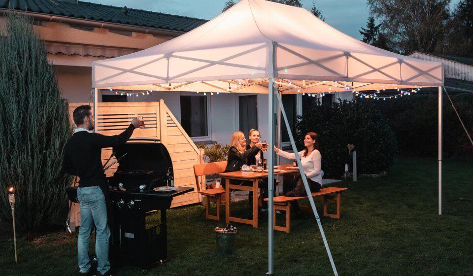 Der weiße Faltpavillon dient den drei weiblichen Gästen, die auf einer Rustica-Designgarnitur im Garten ihren Grillteller genießen, als Überdachung. Der Herr am Grill erhebt sein Glas Bier und prostet seinen Gästen zu.