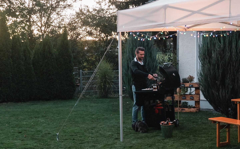 Der weiße Faltpavillon wurde mit Spanngurten und Heringen in der Wiese gesichert. Der Mann im Hintergrund steht am Grill und bereitet das Fleisch zu.