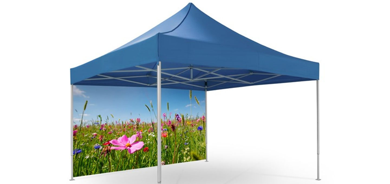 Blaues Gartenzelt mit einer geschlossenen Seitenwand hinten, welche mit einer Blumenwiese bedruckt ist.