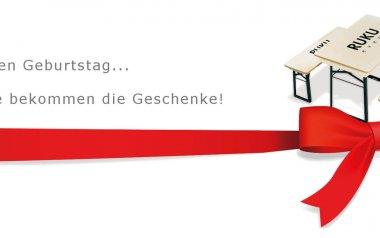 """Shorty-Garnitur mit RUKUevent-Logoaufdruck und Aufschrift """"Wir haben Geburtstag... Sie bekommen die Geschenke!"""", eingehüllt in roter Schleife, anlässlich des 25-jährigen Jubiläums der HBS GmbH"""