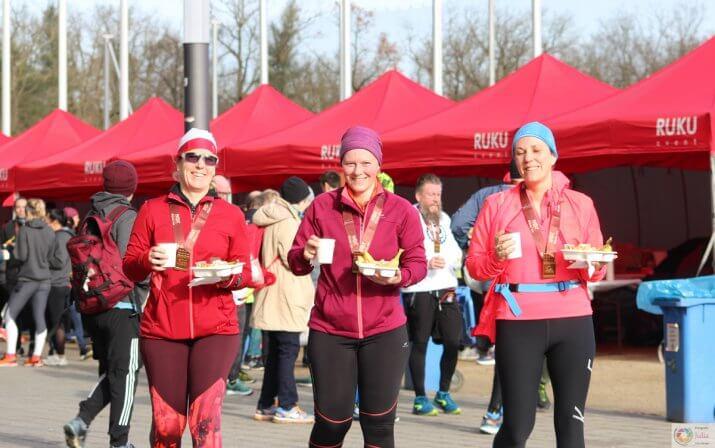 Drei Frauen mit Essen und Getränke in der Hand beim Hot Chocolate Winter Run.