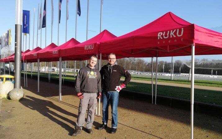 Zwei Herren stehen vor den aneinandergereihten Faltpavillons von RUKUevent beim Hot Chocolate Winter Run.