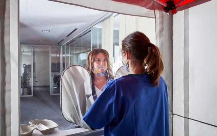 Eine Frau steht in der Indoor-Testkabine und legt ihre Hände in die Armgamaschen. Hinter der Trennwand, außerhalb der Kabine befindet sich eine Frau. Die Kabine steht in einem Gebäude.