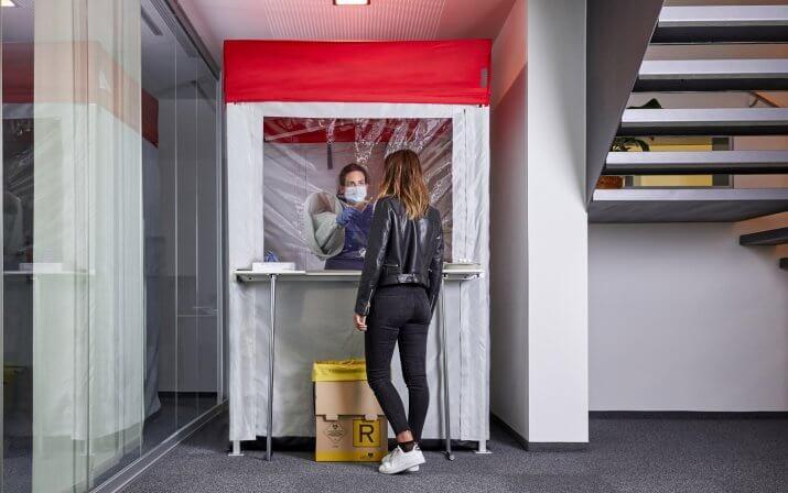 In der indoor Test Kabine befindet sich eine Frau, die ihre Arme durch die Armgamaschen steckt, um bei der Person außerhalb der Kabine hinter der Schutzwand einen Schnelltest vorzunehmen. Die Testkabine ist in einem Gebäude aufgestellt.