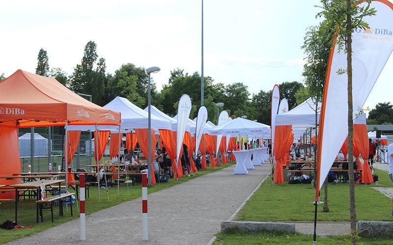 Faltpavillons mit weißen Dächern und orangen Eckvorhängen aneinander gereiht.