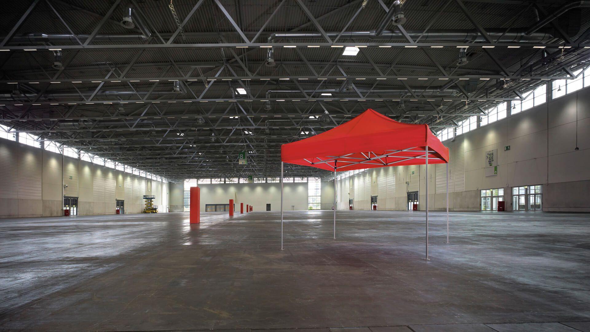 Roter Faltpavillon ohne Seitenwände in einer großen Halle.