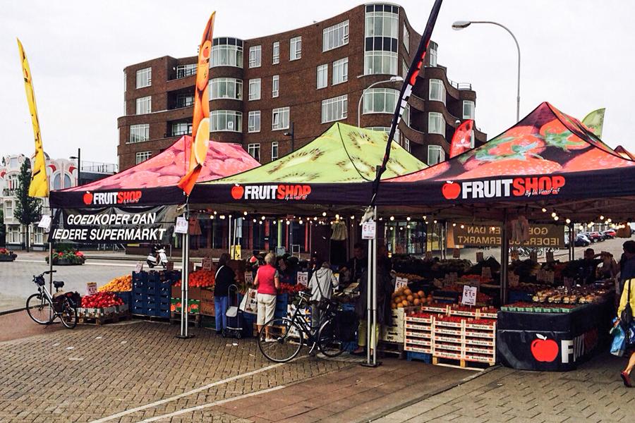 3 Marktzelte auf einem Obstmarkt in verschiedenen Größen und unterschiedlicher Bedruckung. Fruit Shop ist auf dem Marktzelt aufgedruckt.