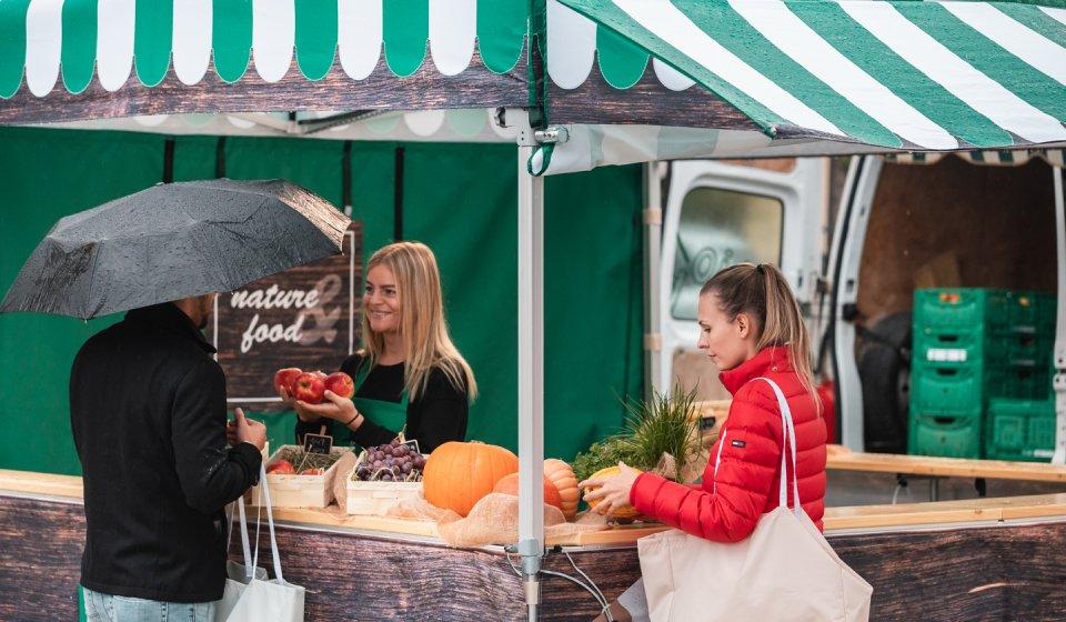 Die Verkäuferin im Marktstand überreicht dem Kunden vier Äpfel. Der Kunde schützt sich mit einem Regenschirm vor dem Regen. Eine weitere Kundin hingegen wird vom Vordach des Marktzeltes vor dem Regen geschützt.