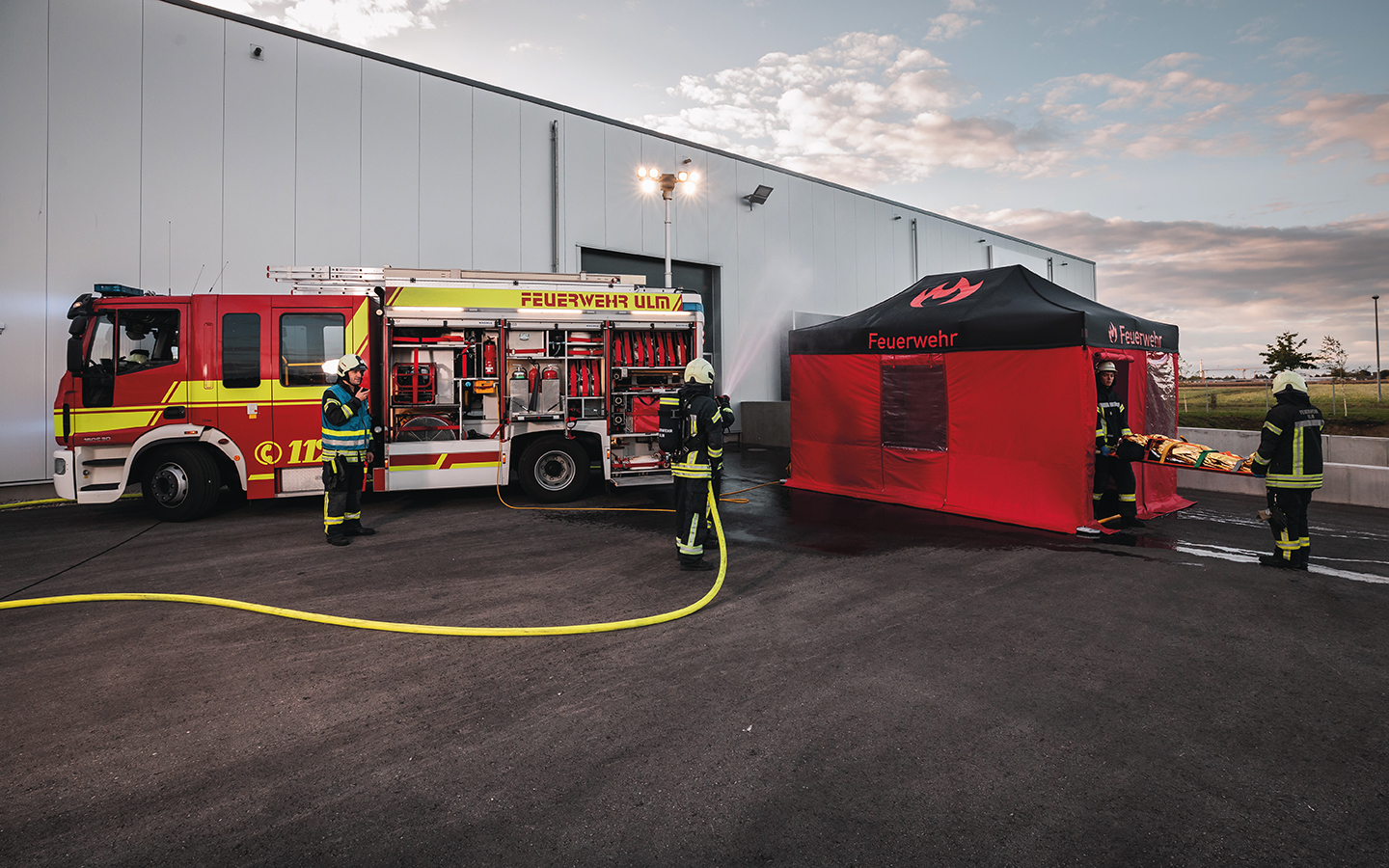 Two firefighters bring an injured person into the black and red firefighting canopy tent, which is set up right next to the fire truck. While another firefighter sprays the building hall with water, the firefighter with the radio directs the operation.