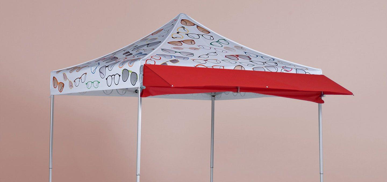 Weißer bedruckter Faltpavillon mit einem roten Vordach, welches man jederzeit ab- und anmontieren kann.