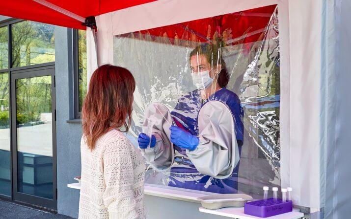 In der outdoor Test Kabine befindet sich eine Frau, die ihre Arme durch die Armgamaschen steckt, um bei der Person außerhalb der Kabine hinter der Schutzwand einen Schnelltest vorzunehmen.