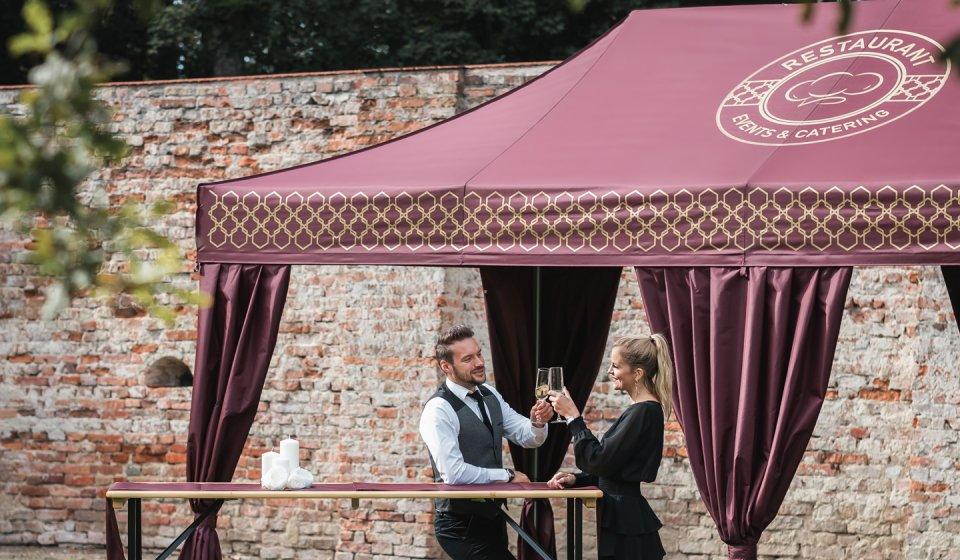 Zwei elegant gekleidete Gäste lehnen vor einem eleganten Faltpavillon mit Eckvorhängen an einem Stehtisch an und stoßen mit Sektgläsern an.