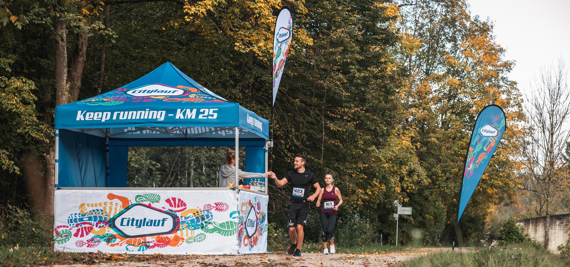 Bunt bedrucktes Promotionzelt wird als Verpflegungsstation bei einem Marathon genutzt. Zwei Läufer rennen daran vorbei und nehmen sich eine Banane zur Stärkung.