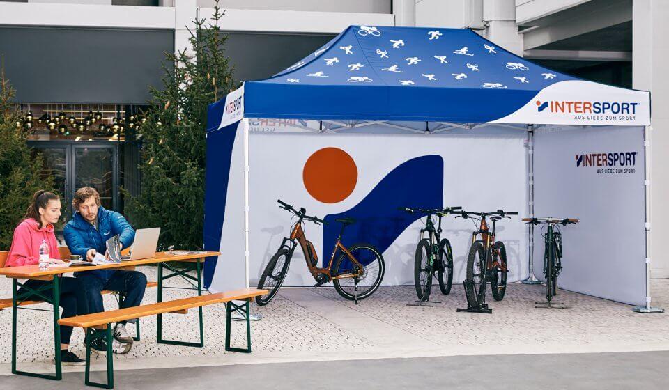 Das personalisierte Promotionzelt von INTERSPORT überdacht vier Fahrräder. Der Verkäufer sitzt mit einer Kundin gleich nebenan auf einer Bierzeltgarnitur und zeigt dieser verschiedene Kataloge.
