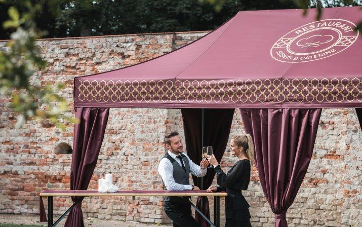 Zwei elegant gekleidete Gäste lehnen an einem Stehtisch vor einem eleganten Faltpavillon mit Eckvorhängen an und stoßen mit Sektgläsern an.