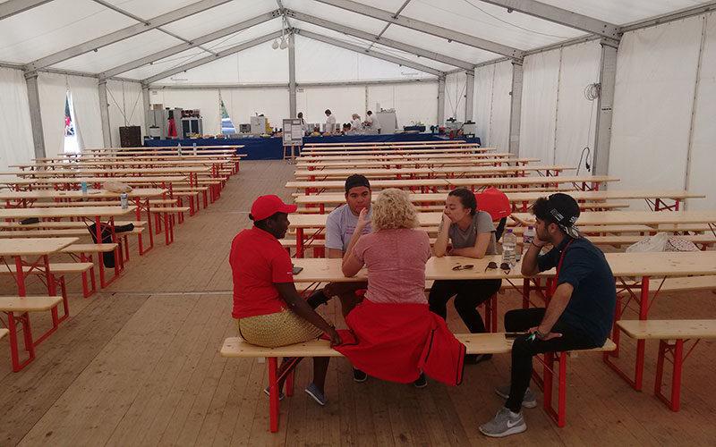 Personen sitzen gemütlich auf Bierzeltgarnituren mit rotem Untergestell