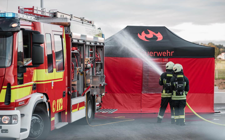Zwei Feuerwehrmänner spritzen Wasser mit dem gelben Schlauch zwischen Feuerwehrauto und wasserdichtem Faltpavillon hindurch.