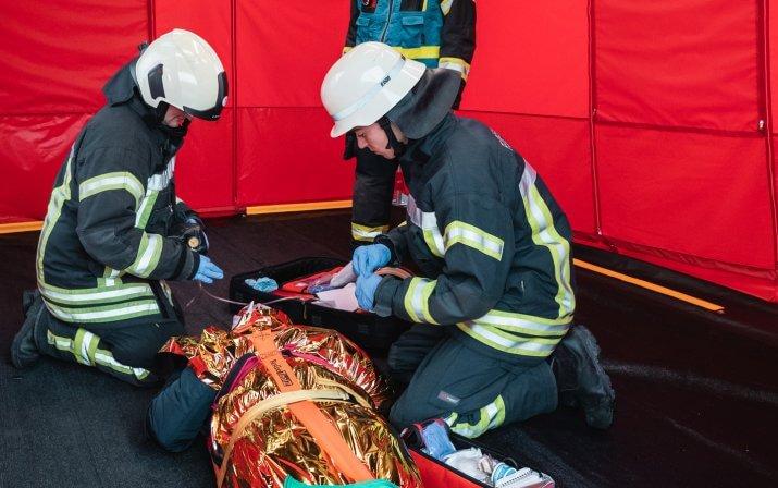 Drei Feuerwehrmänner betreuen eine verletzte Person im mobilen Sanitätszelt.