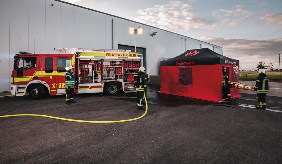 Zwei Feuerwehrmänner bringen eine verletzte Person in den schwarz-roten Feuerwehr-Pavillon, der direkt neben dem Feuerwehrauto aufgebaut ist. Während ein weiterer Feuerwehrmann die Gebäudehalle mit Wasser besprüht, leitet der Feuerwehrmann mit dem Funkgerät den Einsatz.