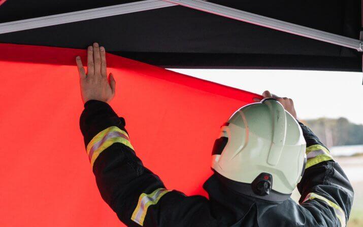 Der Feuerwehrmann bringt die rote Seitenwand am schwarzen Dach des Faltpavillons an. Durch das Aneinanderkleben des Klett- und Flauschstreifens hält die Seienwand am Faltpavillon-Dach.
