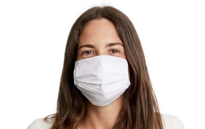 Eine Frau trägt die RUKUevent Schutzmaske aus Stoff in weiß.