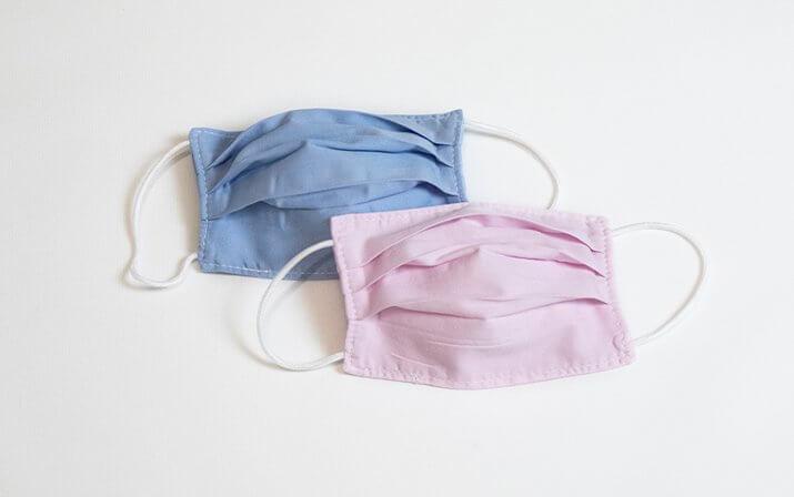 Zwei Kindermasken in den Farben blau und rosa.