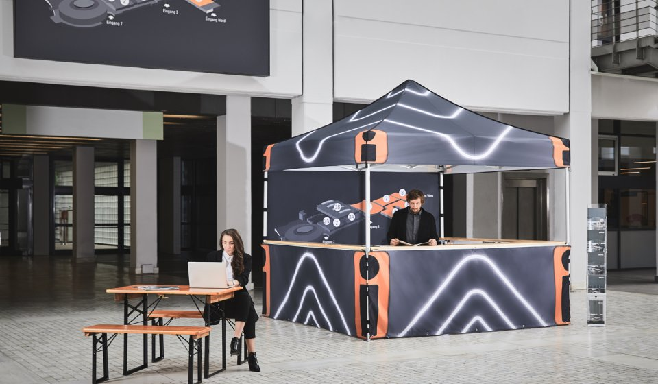 A printed exhibition tent stands at the entrance to the exhibition hall. The salesman in the canopy tent is reading the catalog; the saleswoman is sitting on a short beer garden table set, the