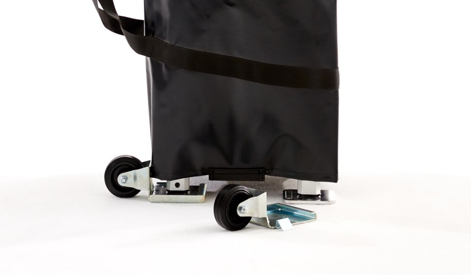 Folded canopy tent in black transport bag with one attached transport wheel. Another transport wheel is in front of the canopy tent.