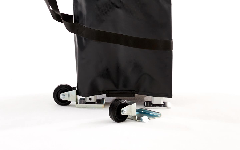 Zusammengefalteter Faltpavillon in schwarzer Transporttasche mit einem angebrachten Transportrad. Ein weiteres Transportrad liegt vor dem Faltpavillon.