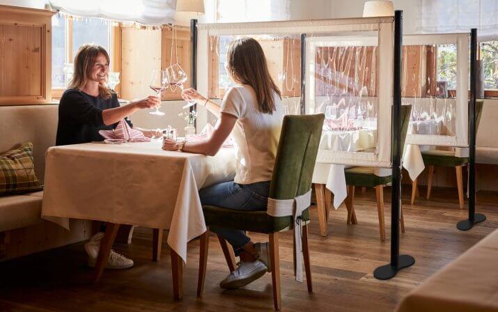 Zwei Damen sitzen im Restaurant und stoßen bei einem Rotwein an. Die jeweils benachbarten Tische und Sitzplätze werden durch Stell- und Schutzwände voneinander getrennt.