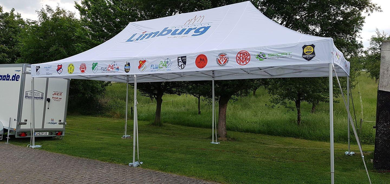 """Weißer Faltpavillon mit """"Limburg"""" aufgedruckt und mit Spanngurten und Bodenplatten befestigt."""