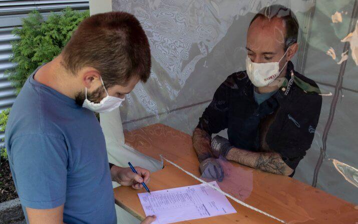 Ein Mitarbeiter steht in der Warenannahme-Station mit einer RUKUevent Schutzmaske-. Auf der anderen Seite steht ein Kunde oder Lieferer, der das Dokument auf der Theke hinter der Schutzwand prüft und unterschreibt.